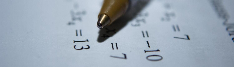 Fotográfia de un bolígrafo sobre una hoja con operaciones matemáticas